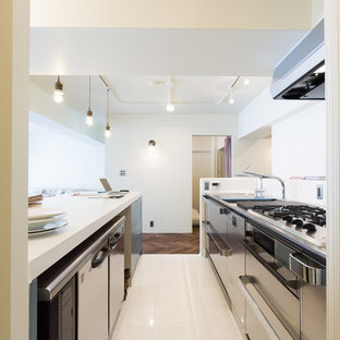 This is an example of an industrial single-wall kitchen in Kobe with an integrated sink, white cabinets, solid surface benchtops, white splashback, porcelain splashback, stainless steel appliances, linoleum floors, with island and white floor.