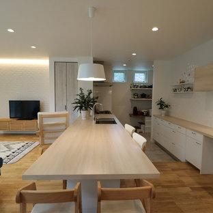 他の地域の北欧スタイルのおしゃれなキッチン (テラコッタタイルの床、グレーの床、シングルシンク、フラットパネル扉のキャビネット、白いキャビネット、木材カウンター、ベージュのキッチンカウンター) の写真