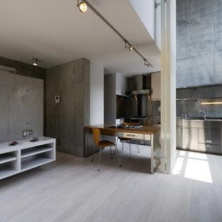 他の地域のインダストリアルスタイルのおしゃれなキッチン (フラットパネル扉のキャビネット、グレーのキャビネット、ステンレスカウンター、グレーのキッチンパネル、シルバーの調理設備の、淡色無垢フローリング、ベージュの床) の写真