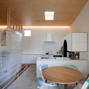 横浜のアジアンスタイルのおしゃれなキッチン (アンダーカウンターシンク、フラットパネル扉のキャビネット、白いキャビネット、白いキッチンパネル、シルバーの調理設備の、黒い床、白いキッチンカウンター) の写真