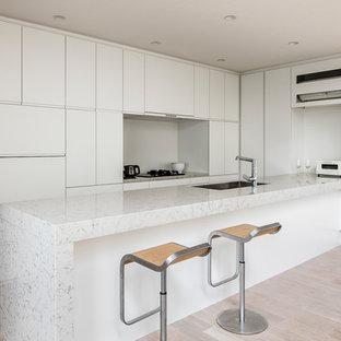 東京23区のII型モダンスタイルのLDKの画像 (シングルシンク、フラットパネル扉のキャビネット、白いキャビネット、大理石カウンター、塗装フローリング、ペニンシュラ型、ベージュの床、白い調理設備)