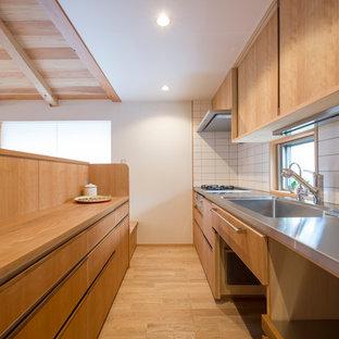 Asiatische Küche mit integriertem Waschbecken, flächenbündigen Schrankfronten, hellbraunen Holzschränken, Edelstahl-Arbeitsplatte, braunem Holzboden, Halbinsel, braunem Boden und brauner Arbeitsplatte in Yokohama