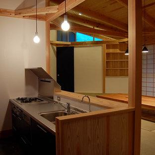 福岡のアジアンスタイルのおしゃれなキッチン (一体型シンク、ステンレスカウンター、黒いキッチンパネル、ガラス板のキッチンパネル、コンクリートの床) の写真