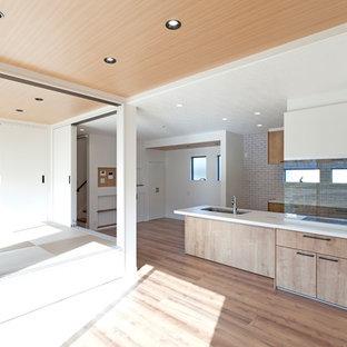 Idee per una cucina moderna di medie dimensioni con lavello a vasca singola, ante a filo, ante beige, top in onice, paraspruzzi bianco, paraspruzzi a finestra, elettrodomestici da incasso, pavimento in compensato, isola, pavimento beige e top bianco