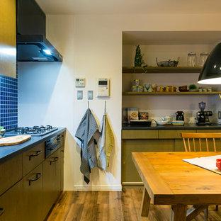 他の地域の北欧スタイルのおしゃれなキッチン (シングルシンク、フラットパネル扉のキャビネット、濃色木目調キャビネット、青いキッチンパネル、塗装フローリング、茶色い床) の写真