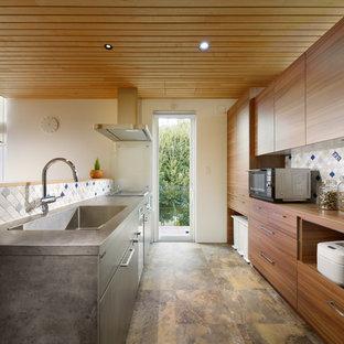 他の地域の北欧スタイルのおしゃれなII型キッチン (一体型シンク、フラットパネル扉のキャビネット、中間色木目調キャビネット、木材カウンター、マルチカラーのキッチンパネル、マルチカラーの床) の写真