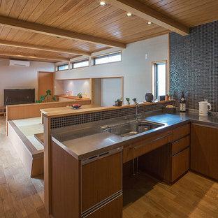 Offene Asiatische Küche ohne Insel in U-Form mit integriertem Waschbecken, flächenbündigen Schrankfronten, hellbraunen Holzschränken, Edelstahl-Arbeitsplatte, Küchenrückwand in Schwarz, Rückwand aus Mosaikfliesen, Küchengeräten aus Edelstahl und braunem Holzboden in Sonstige