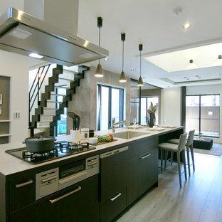大阪のモダンスタイルのおしゃれなキッチン (アンダーカウンターシンク、インセット扉のキャビネット、黒いキャビネット、黒いキッチンパネル、シルバーの調理設備の、ベージュの床、ベージュのキッチンカウンター) の写真
