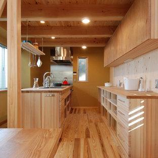 他の地域の北欧スタイルのおしゃれなキッチン (フラットパネル扉のキャビネット、中間色木目調キャビネット、木材カウンター、茶色いキッチンパネル、無垢フローリング、一体型シンク、黒い調理設備、ベージュの床、木材のキッチンパネル、ベージュのキッチンカウンター) の写真