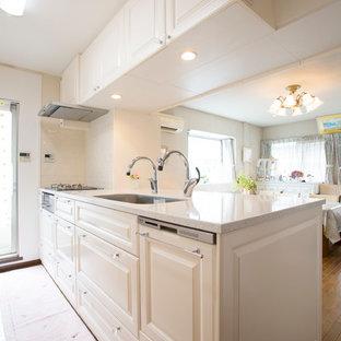 Cette photo montre une cuisine linéaire victorienne avec un évier 1 bac, un placard avec porte à panneau surélevé, des portes de placard blanches, un sol en bois brun, une péninsule, un sol marron et un plan de travail blanc.