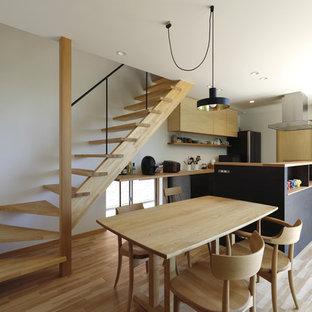 他の地域のラスティックスタイルのおしゃれなキッチン (一体型シンク、フラットパネル扉のキャビネット、黒いキャビネット、ステンレスカウンター、白いキッチンパネル、無垢フローリング、ベージュの床、ベージュのキッチンカウンター) の写真