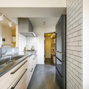 広いコンテンポラリースタイルのおしゃれなII型キッチン (ドロップインシンク、フラットパネル扉のキャビネット、ベージュのキャビネット、白いキッチンパネル、サブウェイタイルのキッチンパネル、シルバーの調理設備、アイランドなし、グレーの床、グレーのキッチンカウンター) の写真