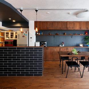 他の地域のアジアンスタイルのおしゃれなキッチン (シェーカースタイル扉のキャビネット、中間色木目調キャビネット、木材カウンター、黒いキッチンパネル、無垢フローリング、茶色い床、茶色いキッチンカウンター) の写真