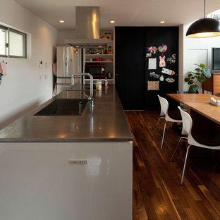 横浜の中サイズのモダンスタイルのおしゃれなキッチン (アンダーカウンターシンク、インセット扉のキャビネット、白いキャビネット、ステンレスカウンター、白い調理設備、濃色無垢フローリング、茶色い床、白いキッチンカウンター) の写真