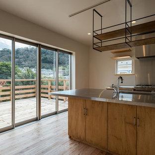 横浜のビーチスタイルのおしゃれなキッチン (アンダーカウンターシンク、フラットパネル扉のキャビネット、淡色木目調キャビネット、ステンレスカウンター、メタリックのキッチンパネル、シルバーの調理設備の、淡色無垢フローリング) の写真