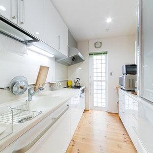 Imagen de cocina de galera, de estilo zen, con fregadero integrado, puertas de armario blancas, salpicadero blanco, suelo de madera en tonos medios y suelo marrón
