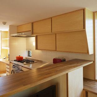東京23区のアジアンスタイルのおしゃれなキッチン (淡色木目調キャビネット、ステンレスカウンター、シルバーの調理設備の) の写真