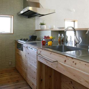 他の地域のモダンスタイルのおしゃれなキッチン (一体型シンク、淡色木目調キャビネット、ステンレスカウンター、緑のキッチンパネル、シルバーの調理設備の、淡色無垢フローリング) の写真
