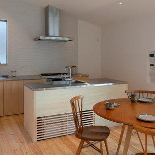 大阪のモダンスタイルのおしゃれなキッチン (淡色無垢フローリング、茶色い床、アンダーカウンターシンク、ステンレスカウンター、白いキッチンパネル、磁器タイルのキッチンパネル、シルバーの調理設備の、ベージュのキッチンカウンター) の写真