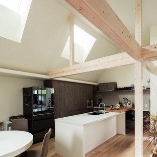 大阪のアジアンスタイルのおしゃれなキッチン (シングルシンク、フラットパネル扉のキャビネット、濃色木目調キャビネット、淡色無垢フローリング、ベージュの床、白いキッチンカウンター) の写真