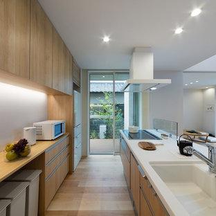 Неиссякаемый источник вдохновения для домашнего уюта: параллельная кухня-гостиная в восточном стиле с монолитной раковиной, плоскими фасадами, фасадами цвета дерева среднего тона, светлым паркетным полом, островом и коричневым полом