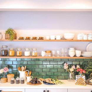 Bild på ett lantligt vit linjärt vitt kök med öppen planlösning, med släta luckor, vita skåp, en halv köksö, en enkel diskho, vitt stänkskydd, rostfria vitvaror, mellanmörkt trägolv och brunt golv