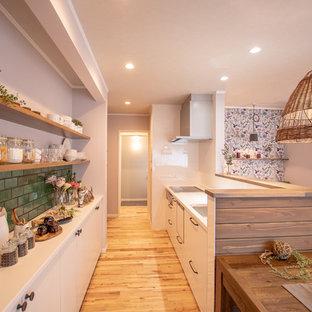 他の地域のカントリー風おしゃれなキッチン (シングルシンク、フラットパネル扉のキャビネット、白いキャビネット、無垢フローリング、茶色い床、白いキッチンパネル、白いキッチンカウンター) の写真