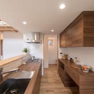 横浜のモダンスタイルのおしゃれなキッチン (シングルシンク、フラットパネル扉のキャビネット、濃色木目調キャビネット、木材カウンター、無垢フローリング、茶色い床、茶色いキッチンカウンター) の写真