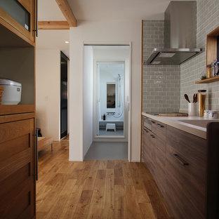 名古屋の北欧スタイルのおしゃれなキッチン (一体型シンク、フラットパネル扉のキャビネット、濃色木目調キャビネット、青いキッチンパネル、無垢フローリング、茶色い床) の写真