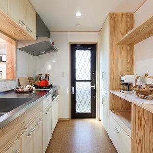 他の地域のアジアンスタイルのおしゃれなキッチン (一体型シンク、フラットパネル扉のキャビネット、淡色木目調キャビネット、ステンレスカウンター、白いキッチンパネル、茶色い床) の写真