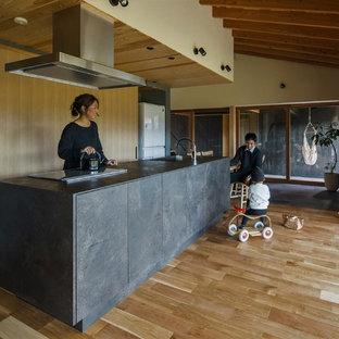 Inspiration för ett mellanstort orientaliskt svart linjärt svart kök med öppen planlösning, med mellanmörkt trägolv, beiget golv, luckor med profilerade fronter, skåp i slitet trä, bänkskiva i terrazo, vitt stänkskydd, stänkskydd i cementkakel och en köksö