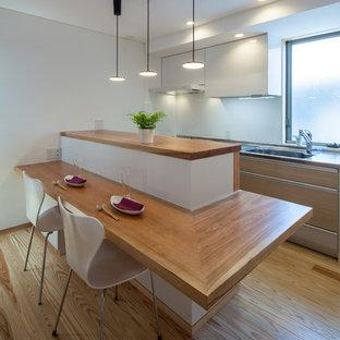 大阪のモダンスタイルのおしゃれなキッチン (アンダーカウンターシンク、フラットパネル扉のキャビネット、淡色木目調キャビネット、ステンレスカウンター、白いキッチンパネル、シルバーの調理設備の、淡色無垢フローリング) の写真