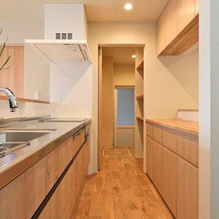 他の地域のモダンスタイルのおしゃれなキッチン (一体型シンク、フラットパネル扉のキャビネット、中間色木目調キャビネット、ステンレスカウンター、白いキッチンパネル、無垢フローリング、茶色い床、茶色いキッチンカウンター) の写真