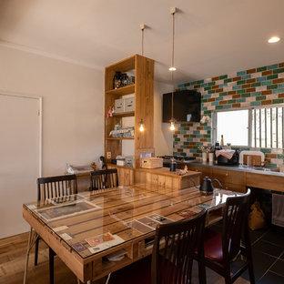 他の地域のラスティックスタイルのおしゃれなキッチン (シングルシンク、フラットパネル扉のキャビネット、中間色木目調キャビネット、ステンレスカウンター、黒い床) の写真