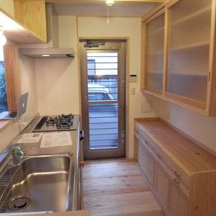 東京都下の小さい和風のおしゃれなコの字型キッチン (一体型シンク、淡色木目調キャビネット、ステンレスカウンター、ガラス板のキッチンパネル、白い調理設備、淡色無垢フローリング、ベージュの床、ベージュのキッチンカウンター) の写真