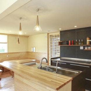 Idee per una cucina a L design con lavello a vasca singola, ante marroni, paraspruzzi blu e parquet chiaro