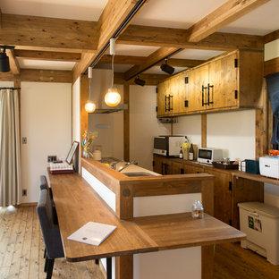 Zweizeilige Asiatische Küche mit Einbauwaschbecken, flächenbündigen Schrankfronten, hellbraunen Holzschränken, Arbeitsplatte aus Holz, braunem Holzboden, Halbinsel, braunem Boden und blauer Arbeitsplatte in Nagoya