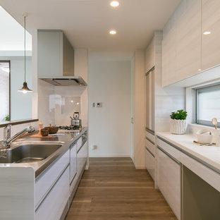 他の地域のコンテンポラリースタイルのおしゃれなキッチン (シングルシンク、フラットパネル扉のキャビネット、グレーのキャビネット、ステンレスカウンター、白いキッチンパネル、無垢フローリング、茶色い床) の写真