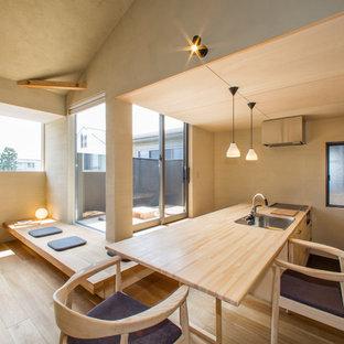 他の地域のアジアンスタイルのおしゃれなキッチン (シングルシンク、フラットパネル扉のキャビネット、淡色木目調キャビネット、木材カウンター、淡色無垢フローリング、茶色い床) の写真