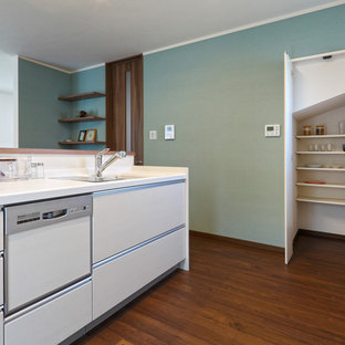 他の地域のコンテンポラリースタイルのキッチンの画像 (一体型シンク、フラットパネル扉のキャビネット、白いキャビネット、白いキッチンパネル、無垢フローリング、アイランド1つ、茶色い床)
