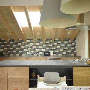 東京23区のアジアンスタイルのおしゃれなキッチン (アンダーカウンターシンク、フラットパネル扉のキャビネット、茶色いキャビネット、人工大理石カウンター、磁器タイルのキッチンパネル、黒い調理設備、セラミックタイルの床、グレーの床、グレーのキッチンカウンター) の写真