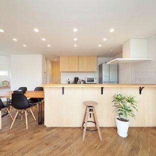 他の地域のモダンスタイルのおしゃれなキッチン (フラットパネル扉のキャビネット、中間色木目調キャビネット、無垢フローリング、茶色い床) の写真
