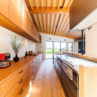 Inspiration for an asian single-wall open plan kitchen in Other with an integrated sink, flat-panel cabinets, stainless steel benchtops, light hardwood floors, with island, brown floor and brown benchtop.