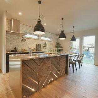 Idéer för att renovera ett industriellt grå grått kök, med en integrerad diskho, bänkskiva i rostfritt stål, vitt stänkskydd, stänkskydd i tunnelbanekakel, ljust trägolv, en köksö och beiget golv