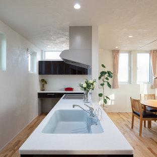 他の地域のアジアンスタイルのおしゃれなペニンシュラキッチン (一体型シンク、淡色無垢フローリング、ベージュの床) の写真