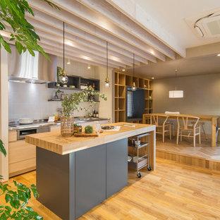名古屋のコンテンポラリースタイルのおしゃれなキッチン (フラットパネル扉のキャビネット、グレーのキャビネット、ステンレスカウンター、グレーのキッチンパネル、淡色無垢フローリング、茶色い床) の写真