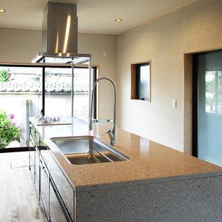 他の地域の巨大な和風のおしゃれなキッチン (シングルシンク、中間色木目調キャビネット、人工大理石カウンター、シルバーの調理設備の、無垢フローリング) の写真