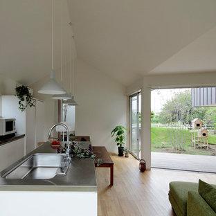 他の地域のコンテンポラリースタイルのおしゃれなキッチン (シングルシンク、フラットパネル扉のキャビネット、白いキャビネット、ステンレスカウンター、白いキッチンパネル、サブウェイタイルのキッチンパネル、白い調理設備、淡色無垢フローリング、茶色い床) の写真