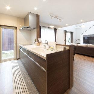 他の地域のコンテンポラリースタイルのおしゃれなアイランドキッチン (一体型シンク、フラットパネル扉のキャビネット、中間色木目調キャビネット、無垢フローリング、茶色い床) の写真