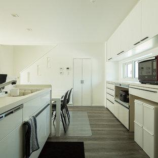 他の地域のモダンスタイルのおしゃれなアイランドキッチン (一体型シンク、フラットパネル扉のキャビネット、白いキャビネット、白いキッチンパネル、グレーの床) の写真
